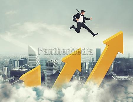 businessman jumps on increasing statistic arrows