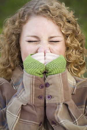 pretty young woman sneezing