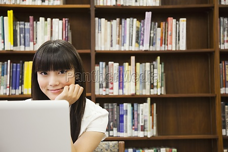 asian woman using laptop in library