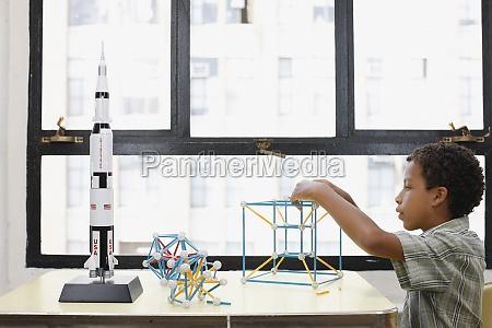 mixed race boy building geometric shape