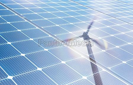 wind turbine reflected in solar panels