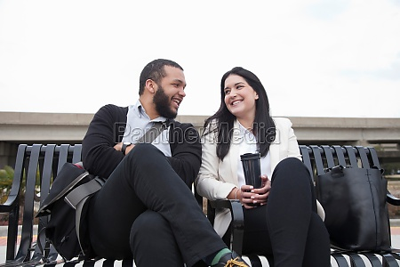young couple sitting on bench on