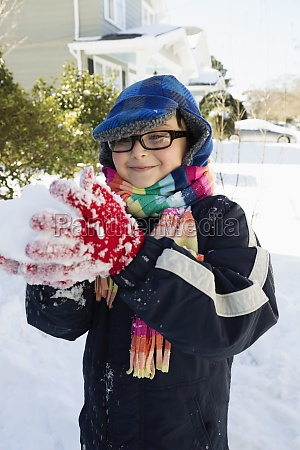 boy making snowball smiling