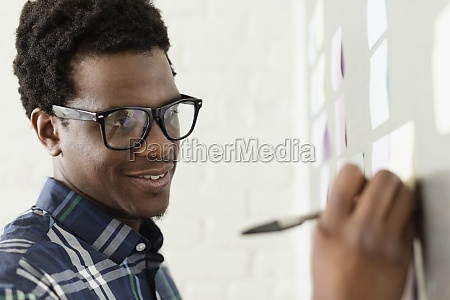 young man wearing glasses writing on