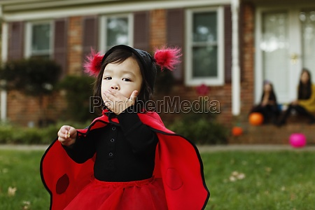 girl dressed as ladybird with hand