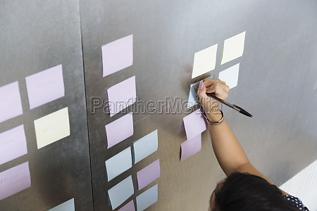 person writing on notes small business