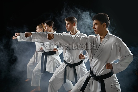 four karate fighters poses in white