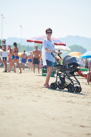 mother walking on beach and push