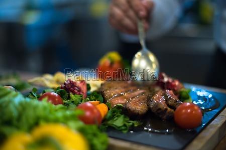 chef hand finishing steak meat plate