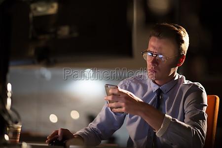 man using mobile phone in dark