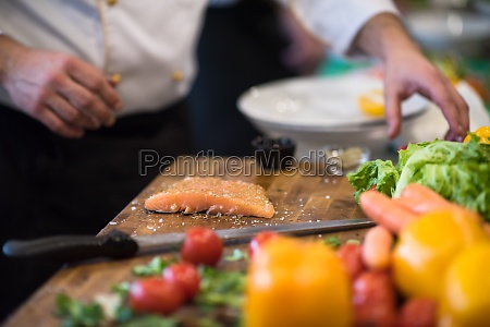 chef hands preparing marinated salmon fish
