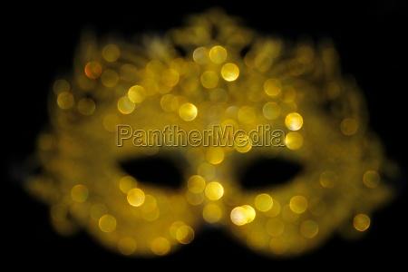 defocused gold glitter carnival mask bokeh