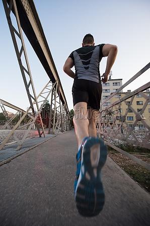 man jogging across the bridge at