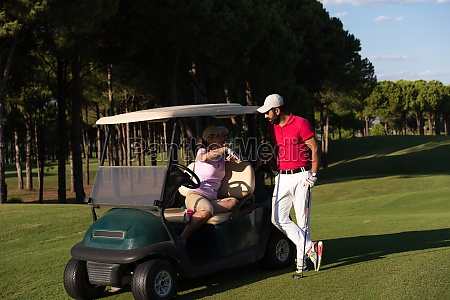couple in buggy on golf course