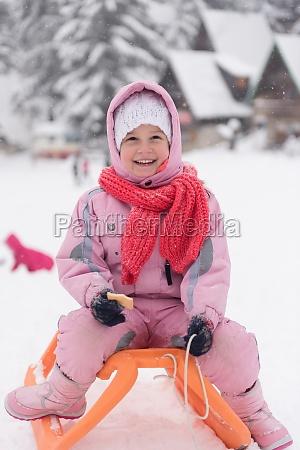 little girl sitting on sledges