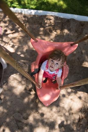 little girl swinging on a