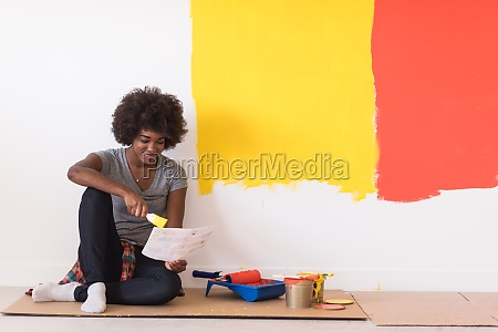 back female painter sitting on floor
