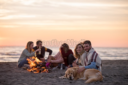 couple enjoying with friends at sunset
