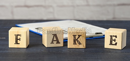 wooden cubes with the inscription fake