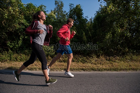 young couple jogging along a country