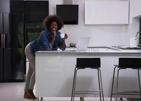 smiling black woman in modern kitchen
