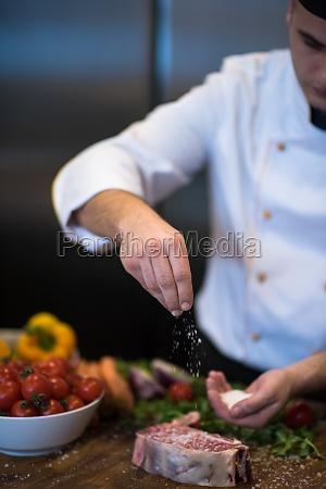 chef putting salt on juicy slice