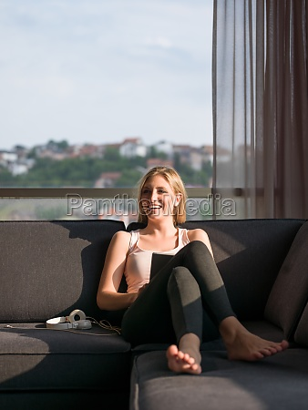 woman using tablet on couch at