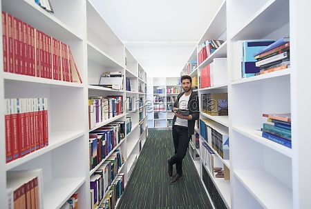 student with tablet in library
