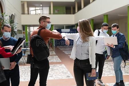 students greeting new normal coronavirus handshake