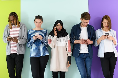 diverse teenagers use mobile devices while