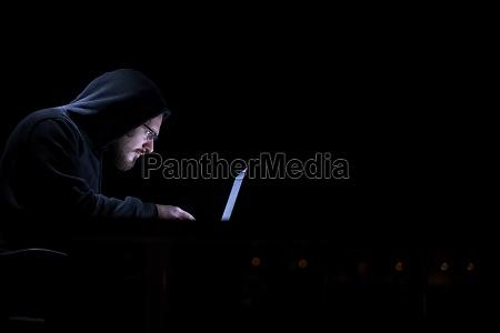 hacker using laptop computer while working