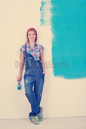happy smiling woman painting interior of