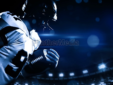 american football player holding ball while