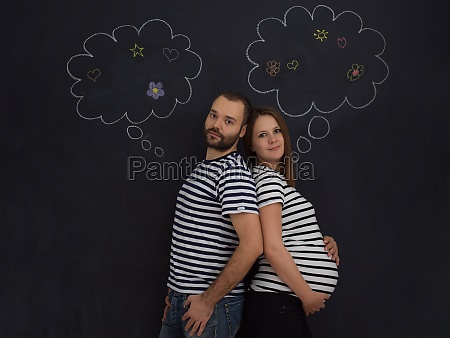 pregnant couple posing against black chalk
