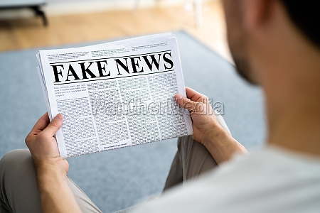 businessman reading fake news article on