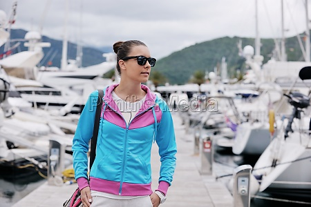 relaxed young woman walking in marina