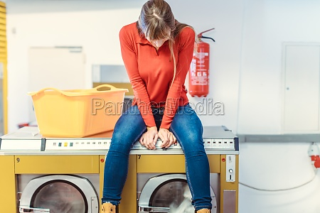 woman sits on washing machine in
