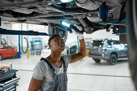 male mechanic checks car suspension auto