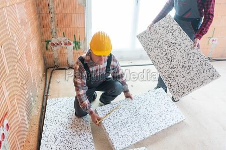 craftsman measuring tile with ruler