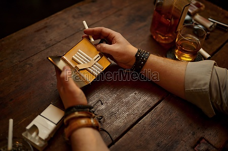 serious man holds cigarette case