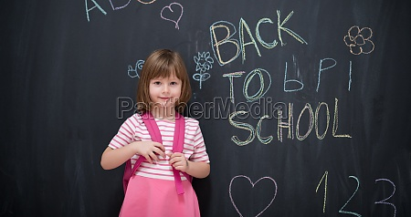 school girl child with backpack writing