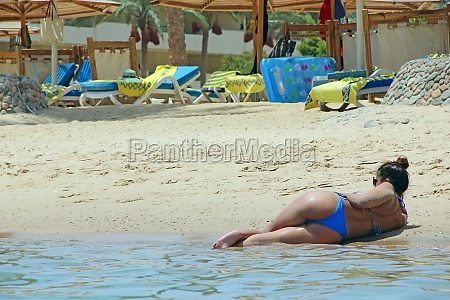 sexy girl lies on sand by