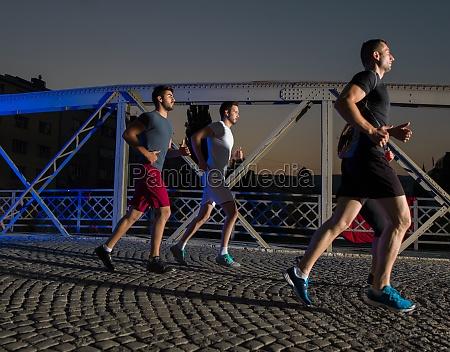 young people jogging across the bridge