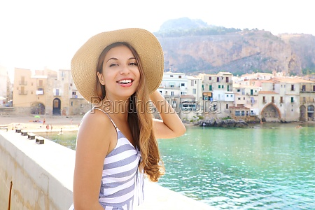 smiling woman holds straw hat on