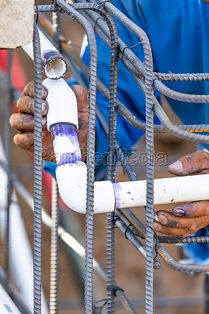 plumber installing pvc pipe at construction