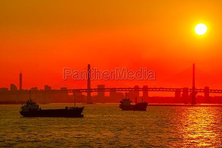 cargo ship silhouette and yokohama skyline