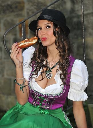 dirndle girl eating pretzel