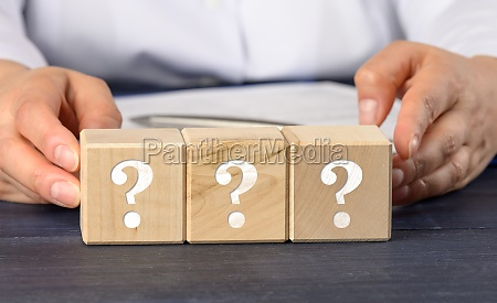 woman holding wooden cubes with question