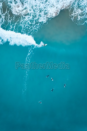 aerial view of surfers at sunset