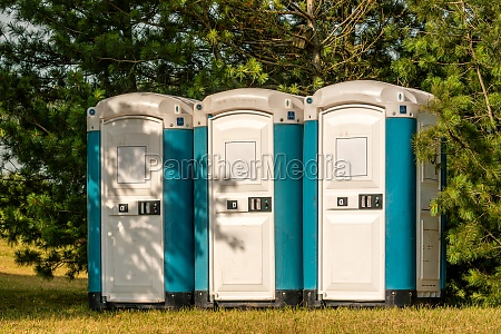 three plastic portable toilets